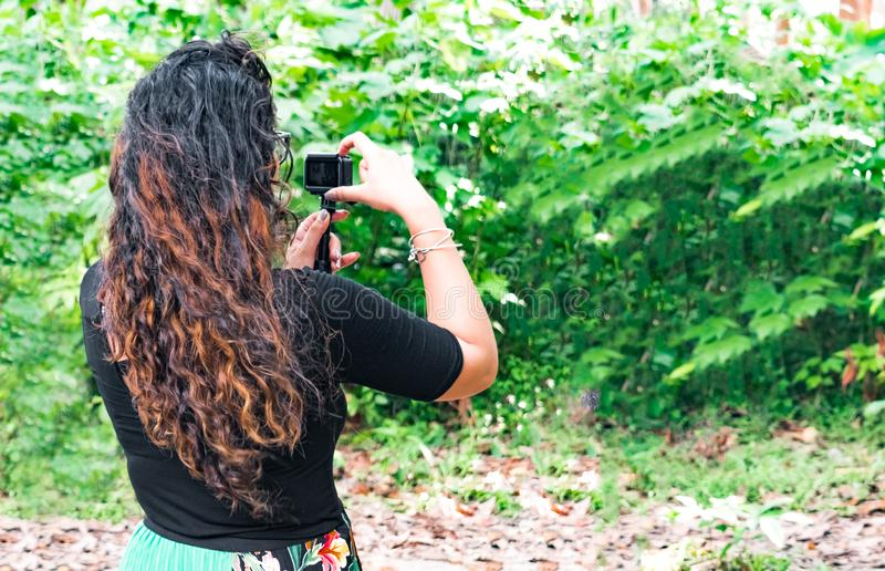 Trendy brunette botanist in her 20s with curly hairs, monitoring plants growth during field work royalty free stock photos