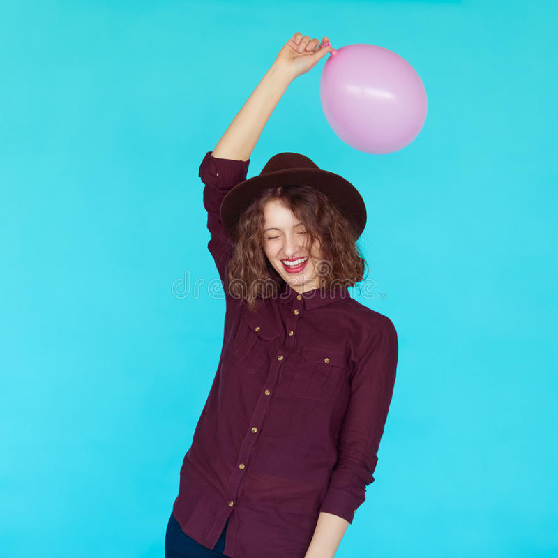 Trendy brunette girl wearing stylish hat, holding a pink balloon royalty free stock photography