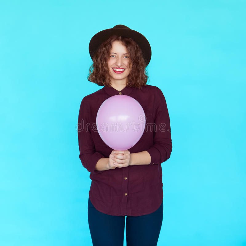 Trendy brunette girl wearing stylish hat, holding a pink balloon royalty free stock images