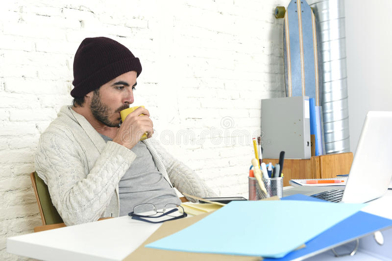 Trendy businessman in cool hipster beanie drinking coffee working happy in at modern home office. Young trendy businessman in cool hipster beanie look drinking royalty free stock photo