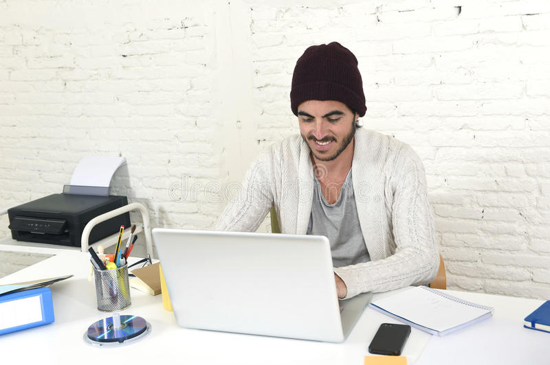 Trendy businessman in cool hipster beanie drinking coffee working happy in at modern home office. Young trendy businessman in cool hipster beanie look smiling royalty free stock photos