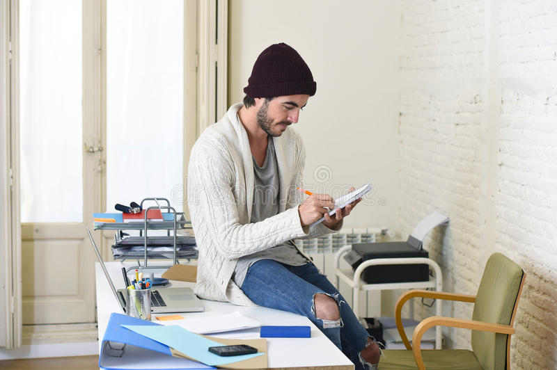 Trendy businessman in cool hipster beanie and informal look writing on pad working at home office. Young trendy businessman in cool hipster beanie and informal stock photos