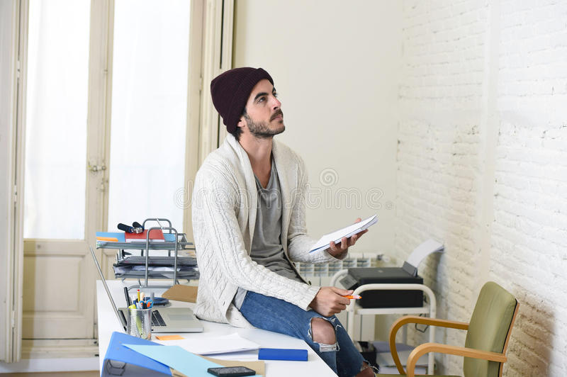 Trendy businessman in cool hipster beanie and informal look writing on pad working thoughtful. Young trendy businessman in cool hipster beanie and informal look stock images
