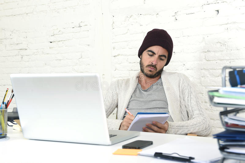 Trendy businessman in cool hipster beanie writing on pad working in at modern home office with computer. Young trendy businessman in cool hipster beanie look royalty free stock photo