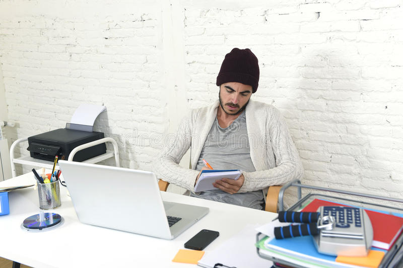 Trendy businessman in cool hipster beanie writing on pad working in at modern home office with computer. Young trendy businessman in cool hipster beanie look stock image
