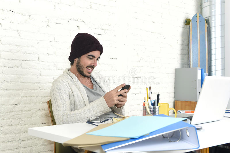 Trendy businessman using internet on mobile phone in freelance business concept. Young trendy businessman in cool hipster beanie look smiling confident at home stock images