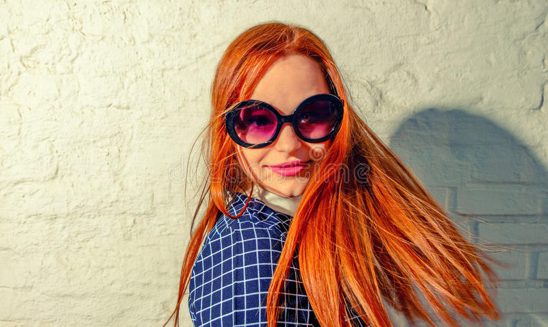 Trendy carrot-top girl turn around with her hair fly about her. Young woman weared in 60th fashion style sunglasses look back. A l stock photo