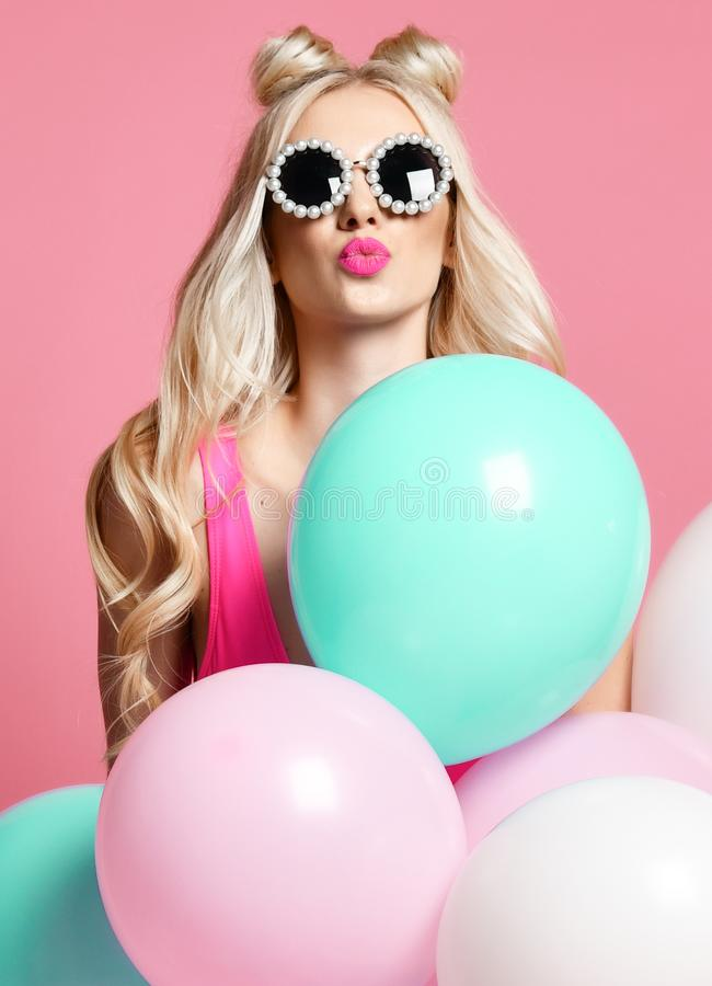 Trendy cheerful blonde woman on birthday party having fun with pastel color air balloons blow kiss stock image