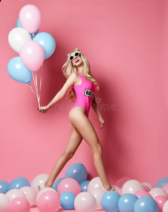 Trendy cheerful blonde woman on birthday party having fun walking with pastel color air balloons stock image