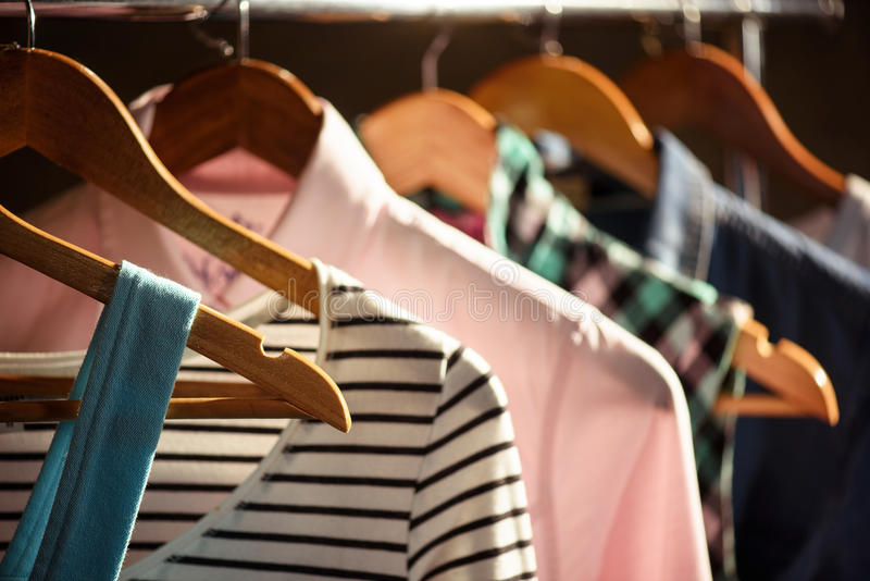 Trendy clothing on wooden hangers royalty free stock photography