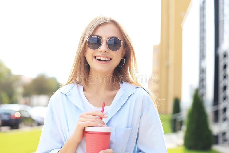 Trendy cool hipster girl drink cocktail in urban city background royalty free stock photo