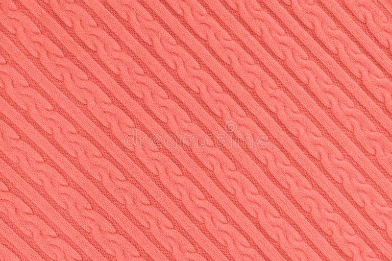 Coral colored Knitwear Fabric Texture. Trendy coral colored Knitwear Fabric Texture with Pigtails and stripes. Repeating Machine Knitting Texture of Sweater royalty free stock photography