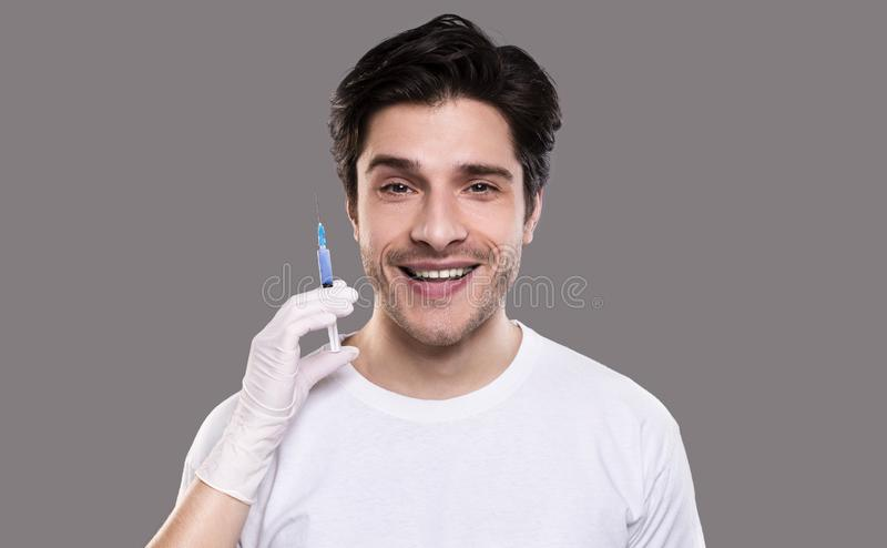 Young man getting beauty injection, grey studio background stock photo