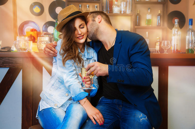 Trendy couple in love celebrates with champagne in a bar. Horizontal photo royalty free stock image