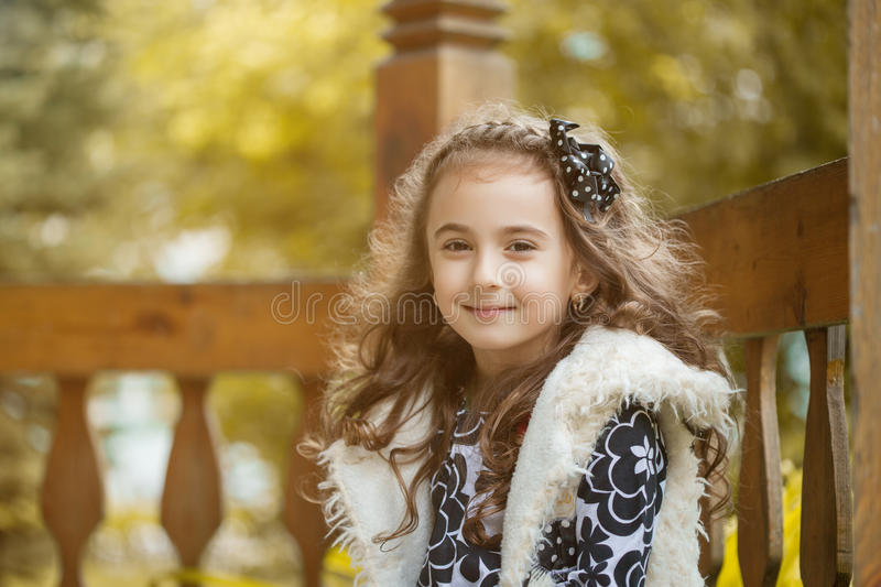 Trendy curly little brunette smiling at camera stock images