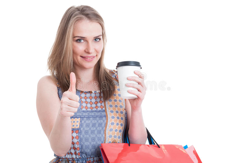 Trendy cute female holding coffee mug and carrying shopping bags royalty free stock photography