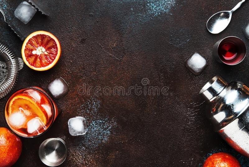 Trendy drink, alcoholic cocktail Negroni with dry gin, red vermouth and red bitter, orange slice and ice cubes. Brown bar counter. Background, bar tools, top stock image