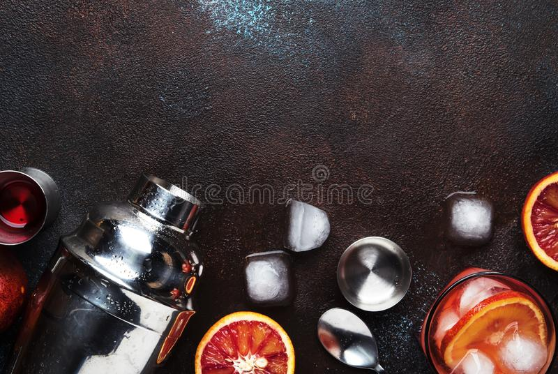 Trendy drink, alcoholic cocktail Negroni with dry gin, red vermouth and red bitter, orange slice and ice cubes. Brown bar counter. Background, bar tools, top royalty free stock photography
