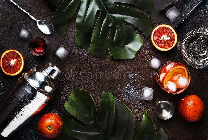 Trendy drink, alcoholic cocktail Negroni with dry gin, red vermouth and red bitter, orange slice and ice cubes. Brown bar counter. Background, bar tools, top royalty free stock images