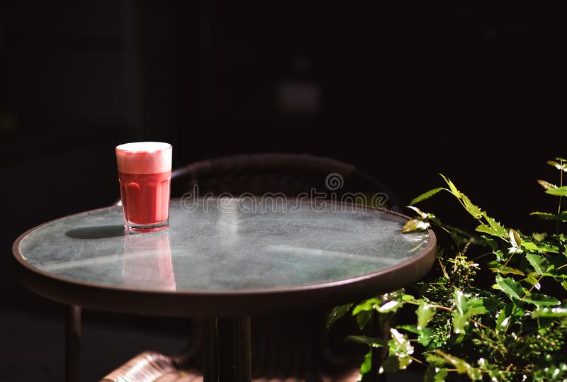 Trendy drink, red berry coffee latte with foam on transparent table in the street cafe royalty free stock photo