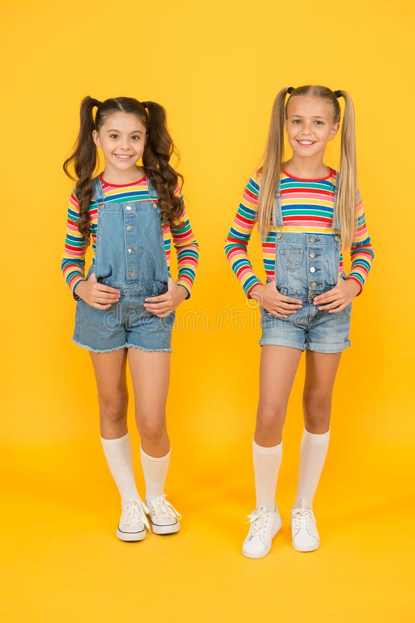 Trendy and fancy. Little girls wearing rainbow clothes. Matching outfits. Fashion shop. Must have accessory. Vibrant. Colors. Modern fashion. Kids fashion stock images