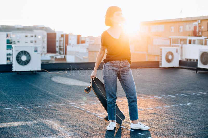 Beautiful girl with longboard talks on phone royalty free stock images