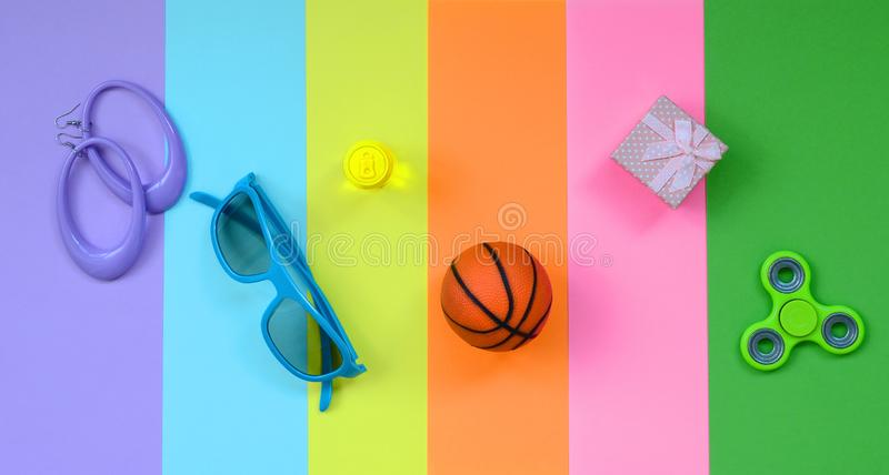 Trendy fashionable pastel composition with earrings, sunglasses, beverage can, basketball ball, gift box and spinner on background. Of pink, violet, green royalty free stock images