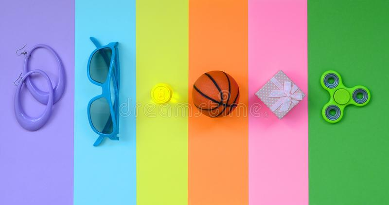 Trendy fashionable pastel composition with earrings, sunglasses, beverage can, basketball ball, gift box and spinner on background. Of pink, violet, green stock photos