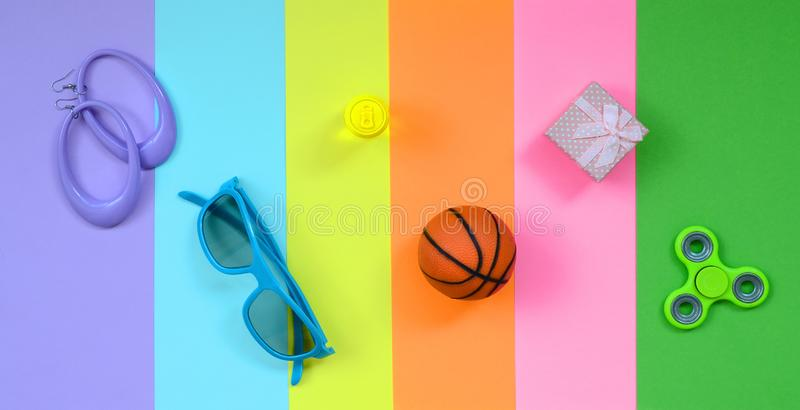 Trendy fashionable pastel composition with earrings, sunglasses, beverage can, basketball ball, gift box and spinner on background. Of pink, violet, green royalty free stock photography