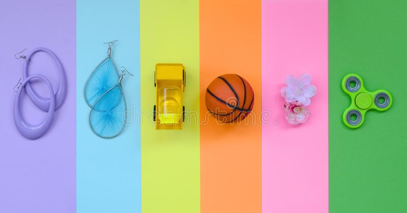 Trendy fashionable pastel composition with earrings, sunglasses, beverage can, basketball ball, toy truck, flower and spinner on. Background of pink, violet royalty free stock photo