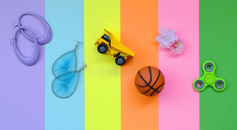 Trendy fashionable pastel composition with earrings, sunglasses, beverage can, basketball ball, toy truck, flower and spinner on. Background of pink, violet stock photography