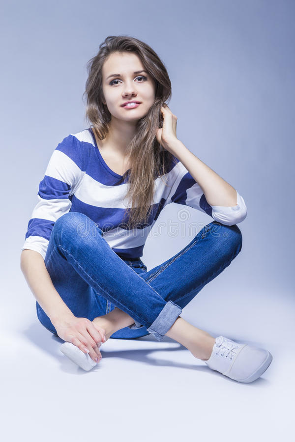 Trendy and Fashionable Positive Caucasian Brunette Girl Sitting On Floor royalty free stock photos