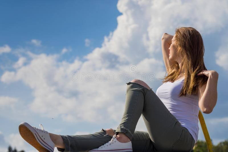 Girl wearing trousers and sneakers relax outdoor. Trendy fashionable woman relaxing outdoor wearing casual footwear white sneakers and hole trousers. Female stock photos
