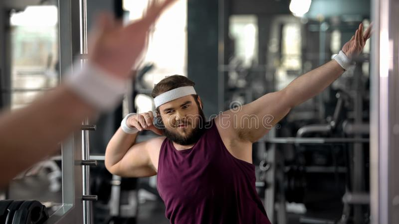 Trendy fat man showing dab move at mirror, satisfied with weight loss results. Stock photo stock image