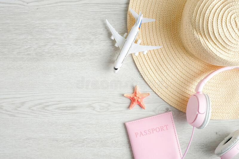 Trendy female travel accessories on wooden background. Top view beach hat, airplane model, passport document and pink headphones. stock images