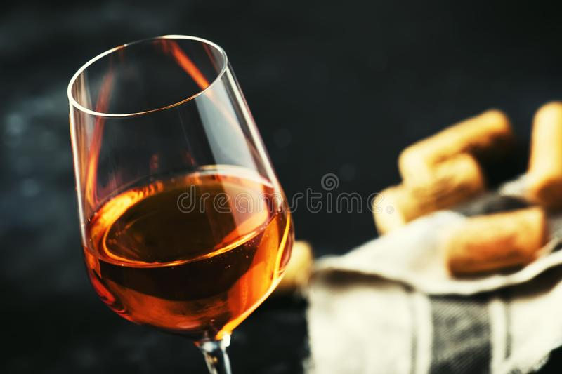 Trendy food and drink, orange wine in glass, gray table background, space for text, selective focus royalty free stock image