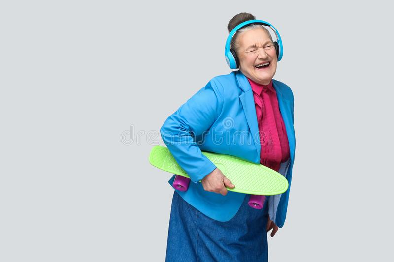 Trendy funny joyful grandmother in colorful casual style with bl stock photo