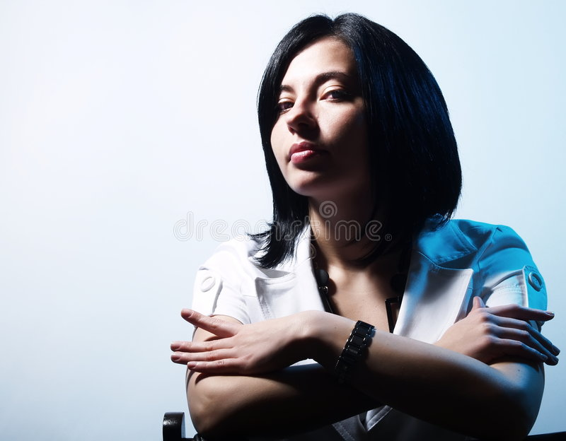 Trendy girl in blue light. A high-key portrait about an attractive trendy girl with black hair who is lighted in blue, she is sitting on a chair and she has a stock photos