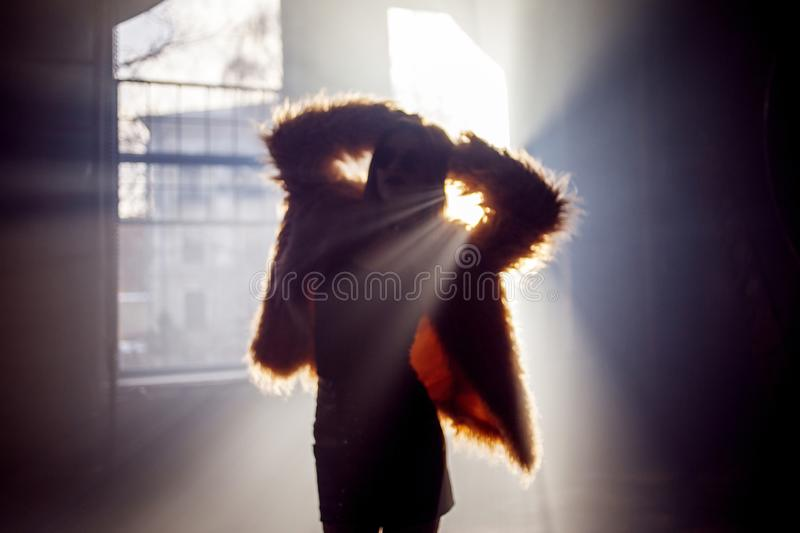 Trendy girl dancing in a fluffy pink coat, blur image. stock photos