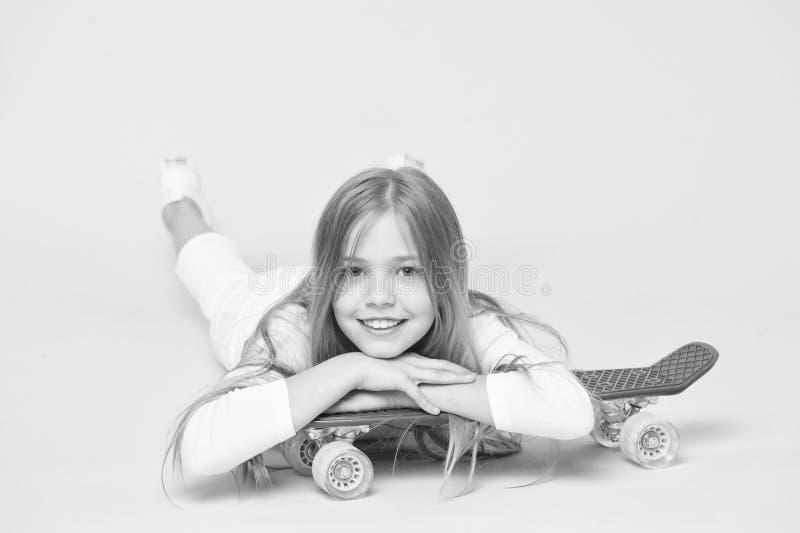 Trendy girl Kid adorable child long hair adore ride penny board Ride penny board en doe trucs Meisje rijdt graag stock fotografie