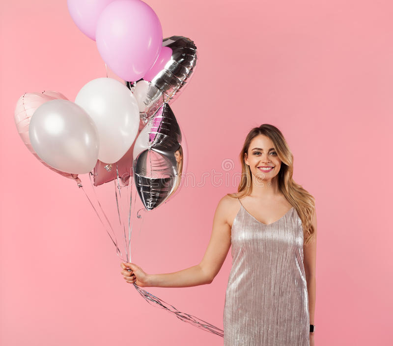 Trendy girl posing with balloons on pink stock photography