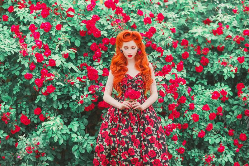 Trendy girl with retro hairstyle with red lips in rose print dress on summer garden. Spring blossom flower. Redhead model in. Trendy summer dress on blossom royalty free stock images