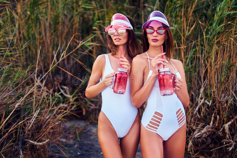 Trendy girls in swimsuits holding lemonades stock photos