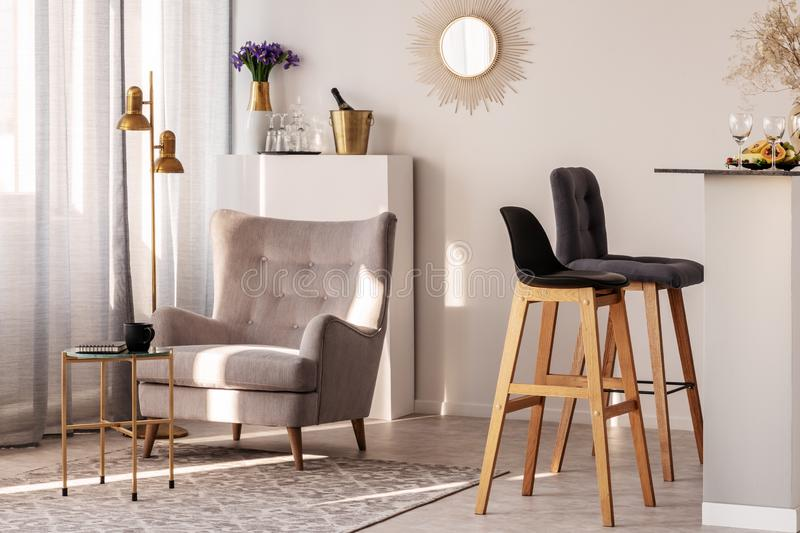 Trendy grey armchair next to two black wooden bar stools in fashionable kitchen and dining room interior. Trendy grey armchair next to two black wooden bar stock images