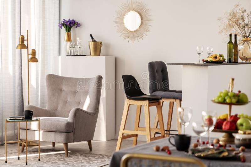 Trendy grey armchair next to two black wooden bar stools in fashionable kitchen and dining room interior. Trendy grey armchair next to two black wooden bar royalty free stock photography