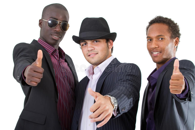 Trendy group of sucCessful businessmen. Young interracial group of teenage businessmen giving a thumbs up sign. Fresh trendy models royalty free stock images