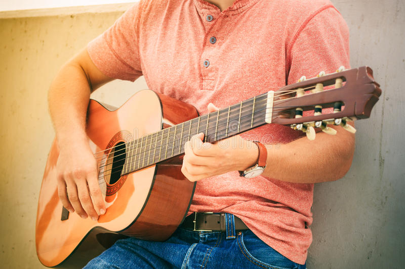 Trendy guy with guitar outdoor. Performance and show on fresh air. Part body of young fashionable man playing classic guitar outdoor. Summer time stock photo