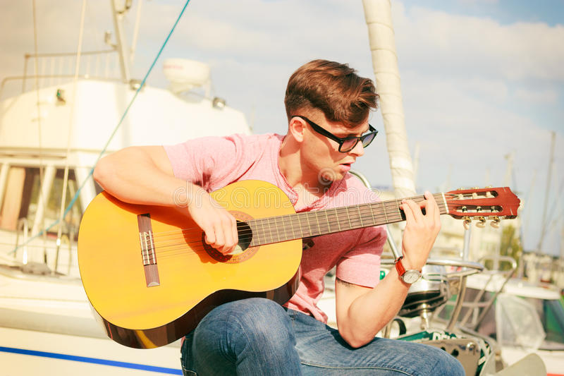 Trendy guy with guitar outdoor. Performance and show on fresh air. Young fashionable man wearing sunglasses playing classic guitar outdoor. Summer time royalty free stock photos