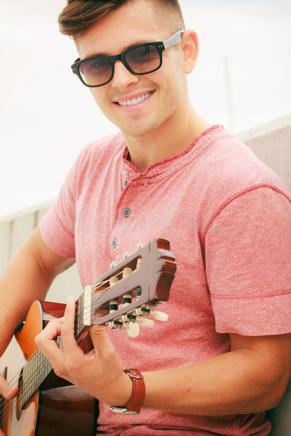 Trendy guy with guitar outdoor. Performance and show on fresh air. Young fashionable man wearing sunglasses playing classic guitar outdoor. Summer time royalty free stock photo