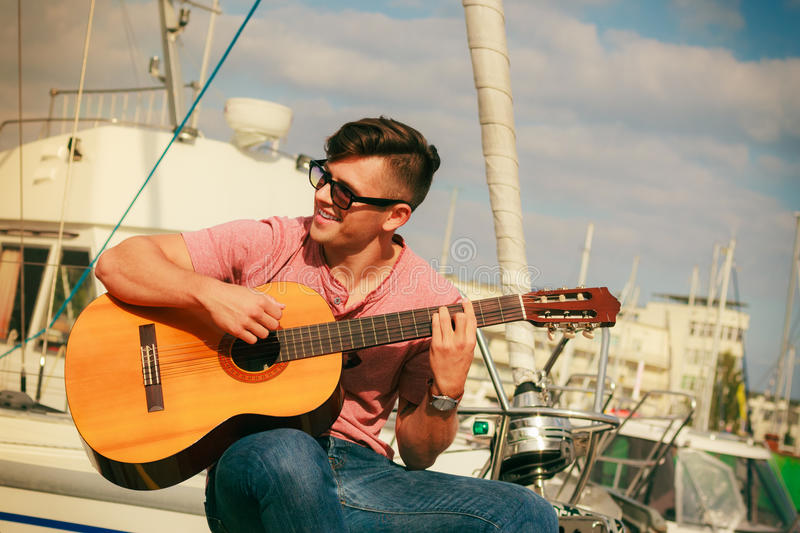 Trendy guy with guitar outdoor. Performance and show on fresh air. Young fashionable man wearing sunglasses playing classic guitar outdoor. Summer time stock photography